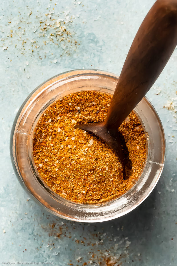 Overhead photo of BBQ spice rub in a glass jar with a spoon inserted into the rub.