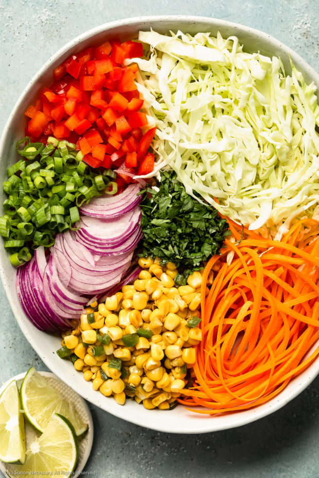 Overhead photo of all the fresh ingredients in Mexican cabbage slaw neatly arranged by individual ingredient in a large white mixing bowl with a ramekin of fresh lime wedges next to the bowl.