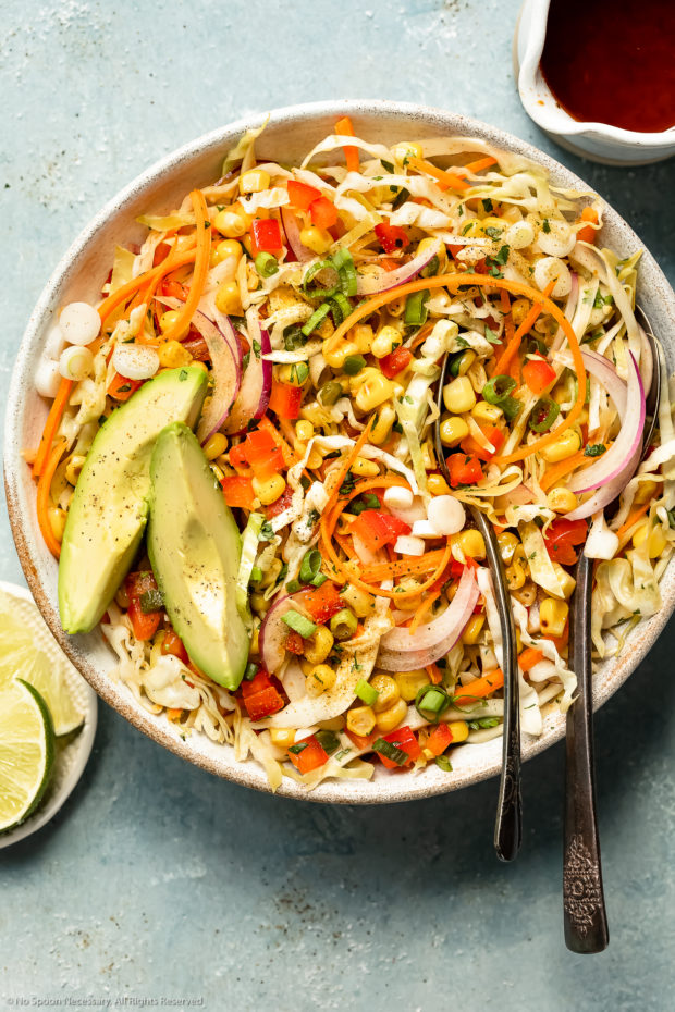 Overhead photo of Mexican coleslaw with corn and avocado in a white bowl with two serving spoons inserted into the slaw and a ramekin of fresh lime wedges and jar of vinaigrette dressing next to the bowl.
