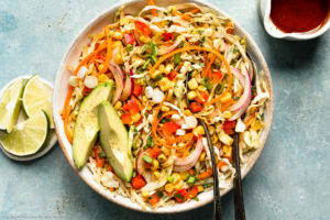 Overhead photo of Mexican coleslaw with corn in a white bowl with two serving spoons inserted into the slaw and a ramekin of fresh lime wedges and jar of vinaigrette dressing next to the bowl.