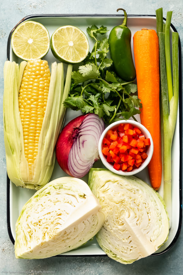 Overhead photo of all the fresh ingredients needed to make Mexican slaw neatly arranged on a large white tray.