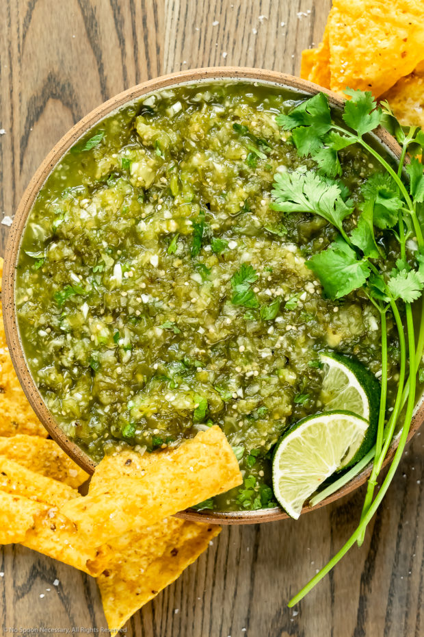 Overhead photo of Salsa Verde topped with lime wedges and fresh cilantro in a neutral colored with yellow tortilla chips scattered around the bowl.