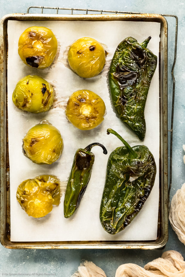 Overhead photo of roasted tomatillos, poblano peppers and a jalapeno pepper on a parchment paper lined sheet pan.