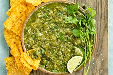 Overhead photo of Salsa Verde topped with lime wedges and fresh cilantro in a neutral colored with yellow tortilla chips scattered around the bowl and a chip inserted into the salsa.