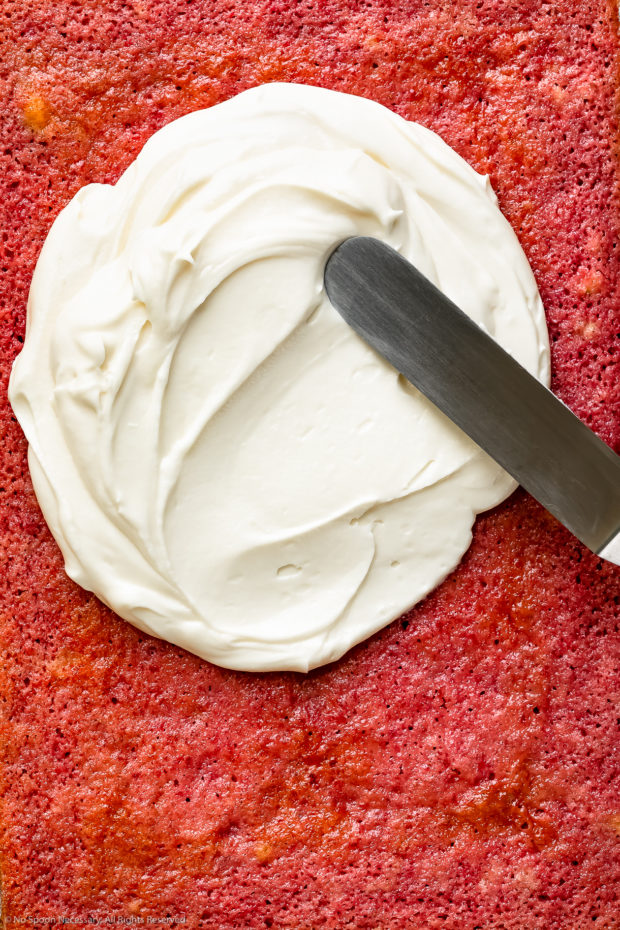 Overhead, up close photo of a strawberry cake being slathered with cream cheese frosting with an offset spatula - photo of step 13 of the recipe.