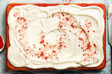 Overhead photo of a Fresh Strawberry Cake topped with cream cheese frosting and dusted with crushed dried strawberries on a blue surface.