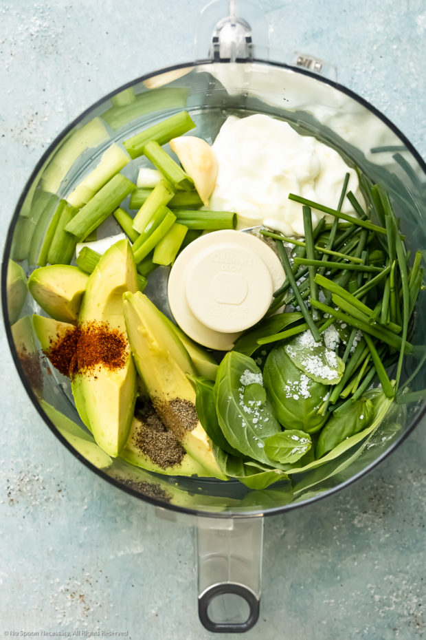 Overhead photo of all the ingredients in avocado green goddess dressing in the bowl of a food processor before being pulsed together.