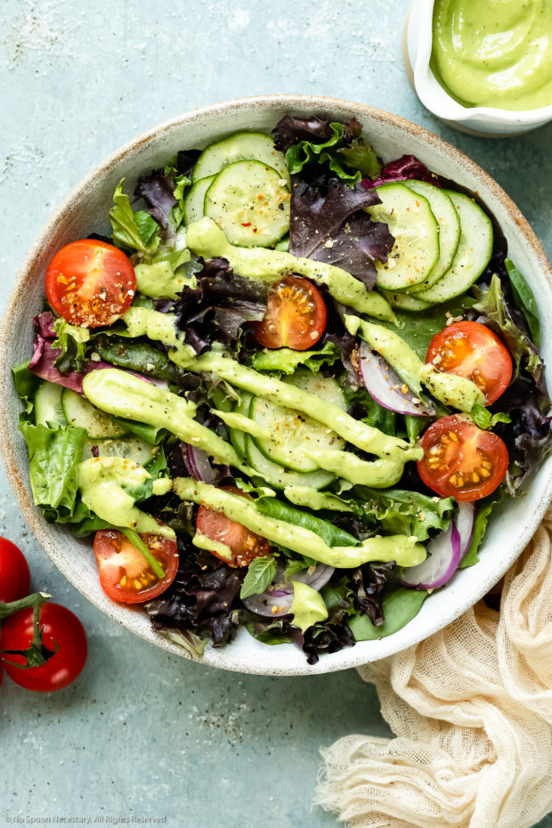 Overhead photo of healthy green goddess dressing drizzled over a leafy green salad with a ramekin of dressing and vine-ripe cherry tomatoes next to the salad - photo showing one way to use dressing.