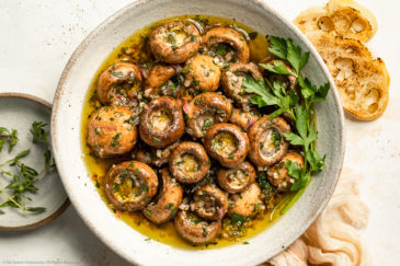 Overhead landscape photo of homemade marinated mushrooms garnished with fresh parsley in a large white serving bowl with slices of artisan bread and a ramekin of fresh thyme next to the bowl.