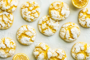 Overhead landscape photo of a dozen Cake Mix Lemon Crinkle Cookies topped with powdered sugar haphazardly arranged on a white wooden board, with fresh halves of lemon scattered around the cookies.