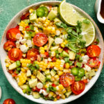 Overhead, landscape photo of Mexican Corn Salad with tomatoes and avocados in a white serving bowl with a jar of honey lime vinaigrette and a ramekin of fresh ground pepper arranged around the bowl.