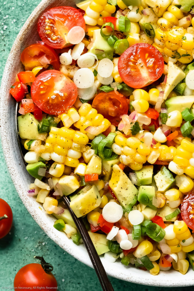 Overhead close-up photo of Corn Tomato Avocado Salad in a white bowl with a serving spoon tucked into the salad.