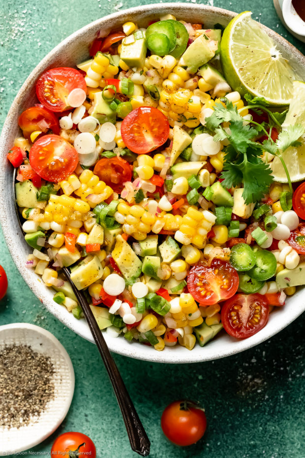 Overhead photo of corn and avocado salad with fresh tomatoes in a white bowl with a serving spoon tucked into the salad and a ramekin of freshly ground pepper next to the bowl.