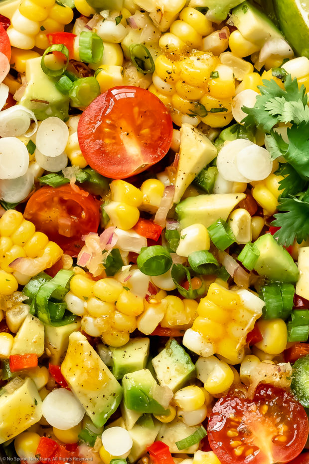 Overhead, extreme up-close photo of Mexican corn salad drizzled with a honey lime vinaigrette.