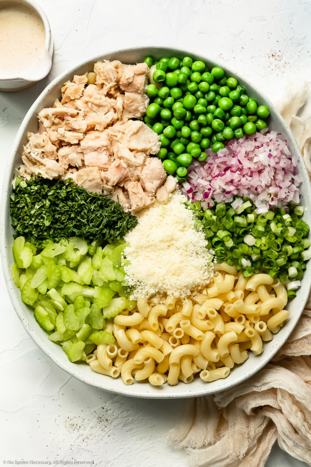 Overhead photo of all the ingredients in tuna macaroni salad neatly arranged in a large white bowl with a ramekin of healthy pasta salad dressing next to the bowl