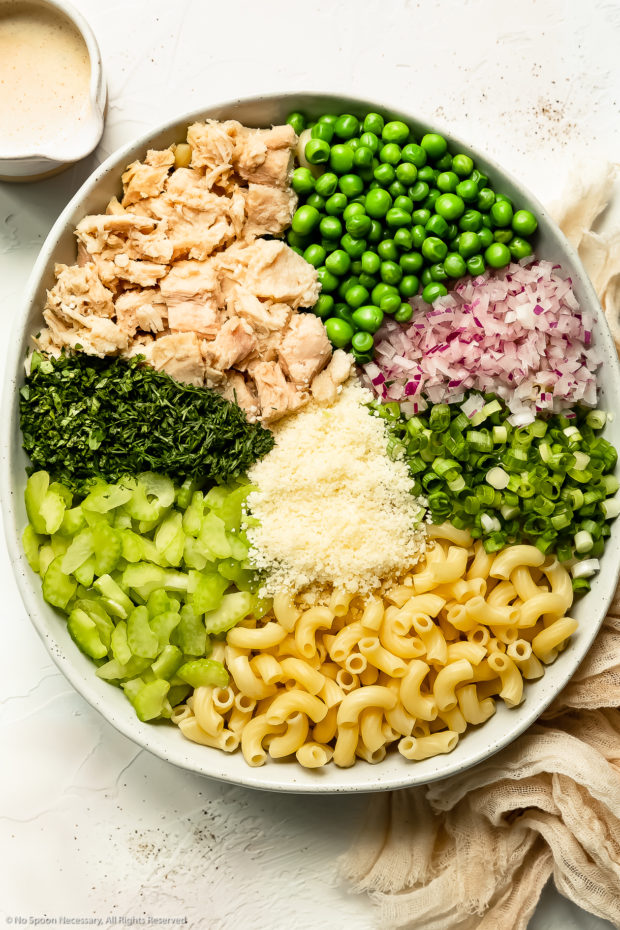 Overhead photo of all the ingredients needed to make tuna macaroni salad neatly arranged by individual ingredient in a large white bowl with a ramekin of healthy pasta salad dressing next to the bowl.