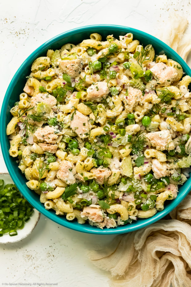 Overhead photo of healthy Tuna Pasta Salad with peas and fresh herbs in a teal serving bowl with a ramekin of sliced scallions and pale tan napkin next to the bowl.