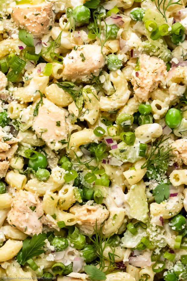 Overhead, close-up photo of healthy pasta salad with tuna, peas and fresh herbs.