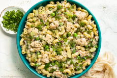 Overhead photo of prepared Tuna Macaroni Pasta Salad with peas and fresh herbs in a teal serving bowl with a ramekin of sliced scallions and pale tan napkin next to the bowl.