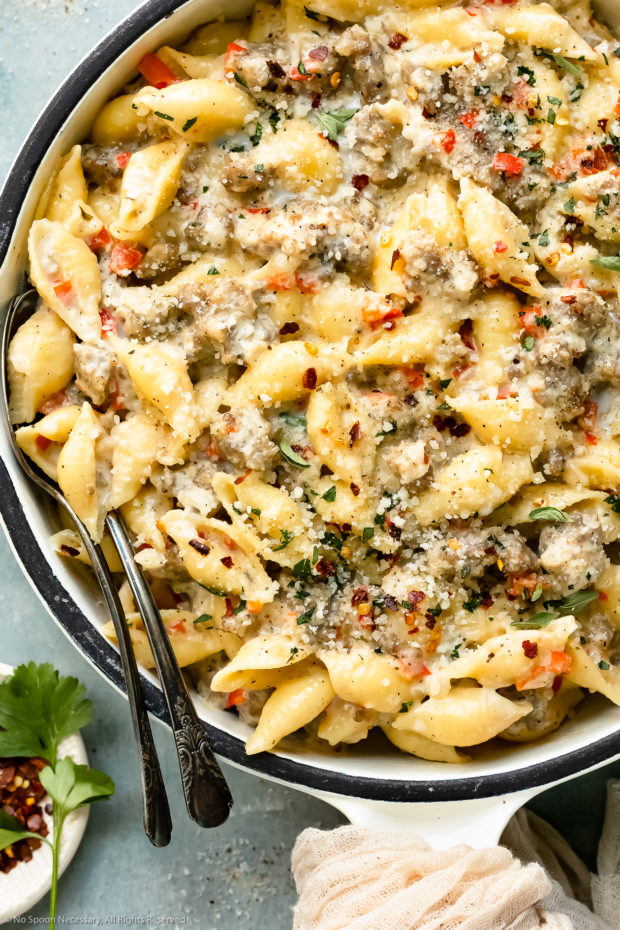 Overhead photo of creamy pasta with spicy Italian sausage in a large white skillet with two serving spoons inserted into the pasta and a ramekin of crushed red pepper flakes next to the skillet.