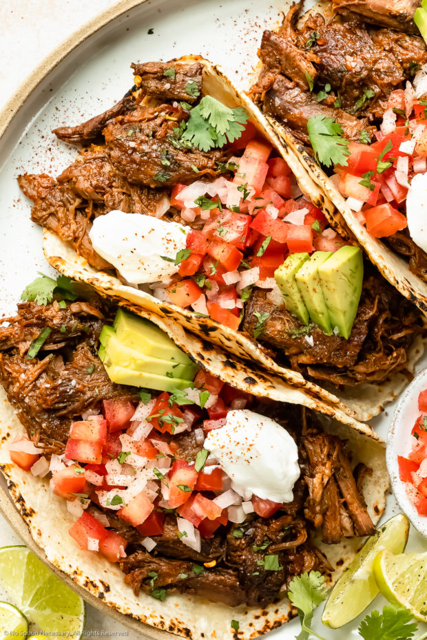 Overhead photo of Mexican Beef Tacos topped with fresh pico de gallo, sliced avocados and sour cream on a white plate with lime wedges next to the tacos.