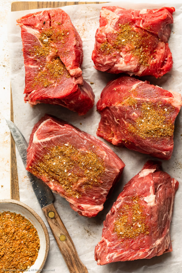 Overhead photo of 3-inch pieces of beef chuck roast sprinkled with Mexican seasonings on a parchment paper lined cutting board.