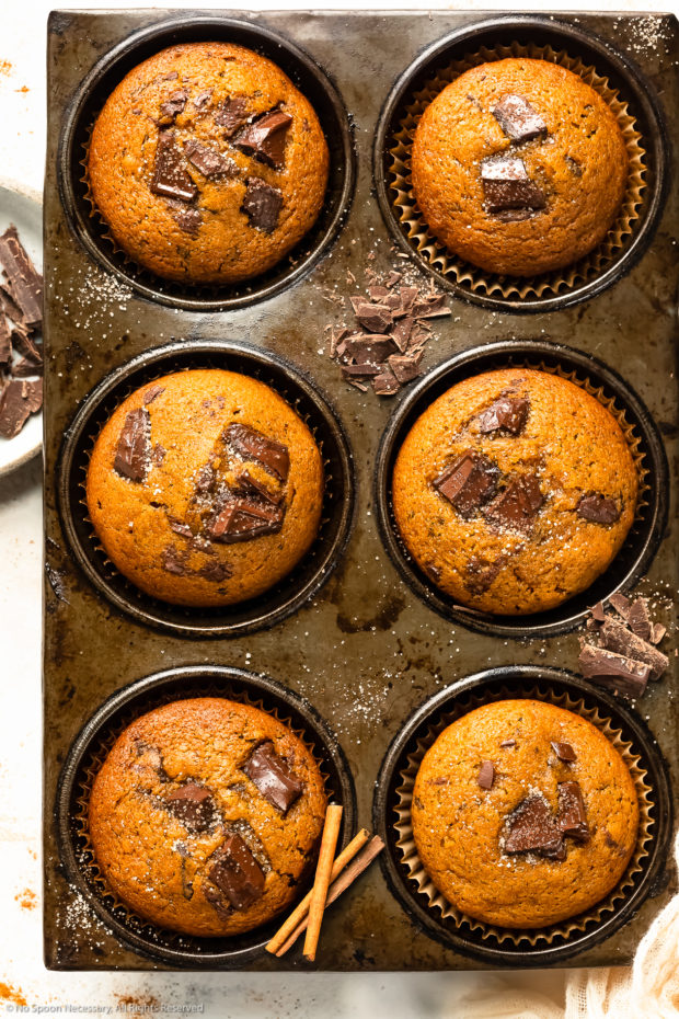 Overhead photo of pumpkin chocolate chip muffins in a muffin pan with roughly chopped dark chocolate and cinnamon sugar strewn on top of the pan.