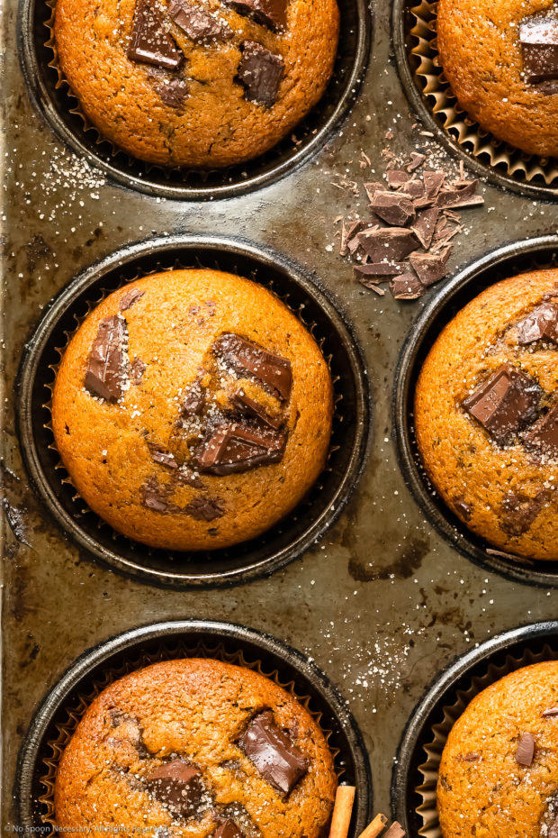 Overhead close-up photo of a pumpkin chocolate chip muffins topped with cinnamon sugar in a muffin pan.