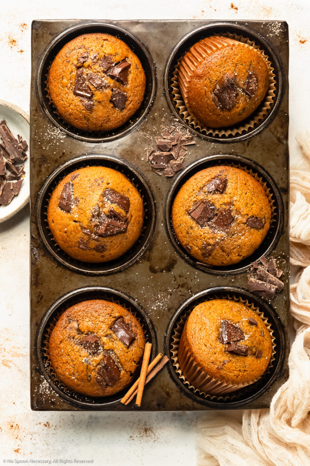Overhead photo of pumpkin chocolate chip muffins in a muffin pan with roughly chopped dark chocolate and cinnamon sugar strewn on top of the pan and a pale tan napkin next to the muffins.