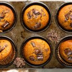 Overhead landscape photo of pumpkin chocolate chip muffins in a muffin pan with roughly chopped dark chocolate and cinnamon sugar strewn on top of the pan.