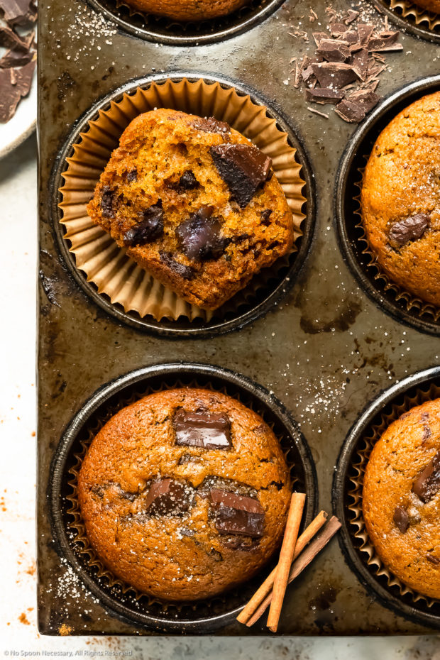 Overhead close-up photo of a halved pumpkin muffin in a muffin pan showcasing the inside texture of the muffin and the large melted chocolate chunks.