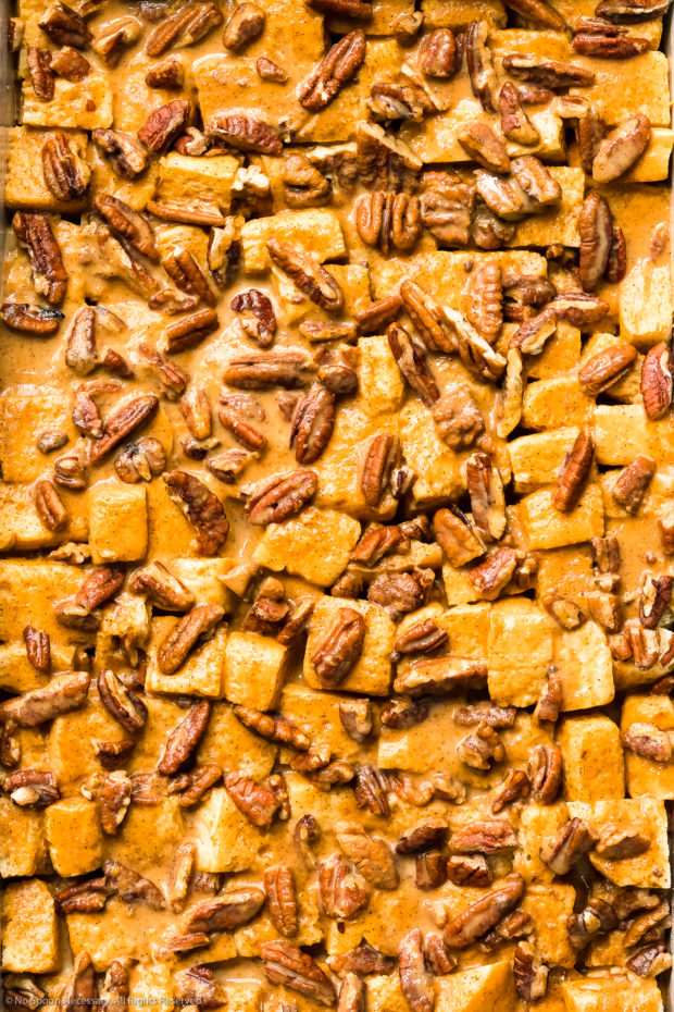 Overhead close-up photo of bread cubes and pecans covered and soaked in a pumpkin egg custard.