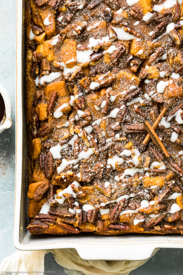 Overhead, close-up photo of Pumpkin French Toast Bake drizzled with cream cheese icing in a white baking dish.