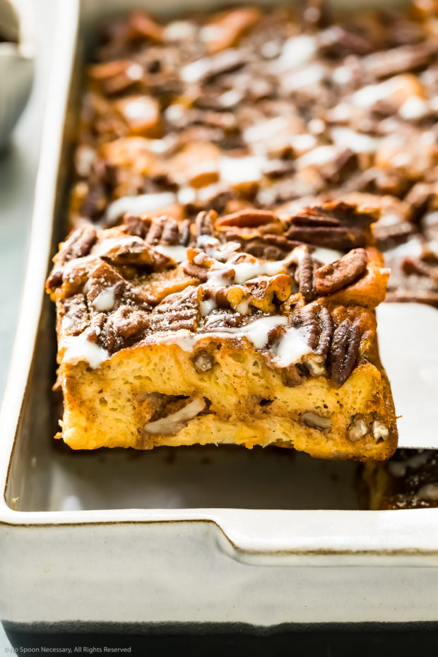 Angled photo of a slice of Pumpkin French Toast being lifted up by a spatula out of a large white baking dish.