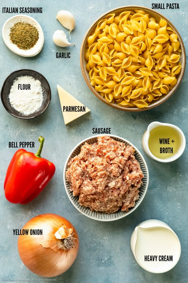 Overhead photo of all the ingredients needed to make sausage pasta neatly organized by individual ingredient with the ingredient name written out.
