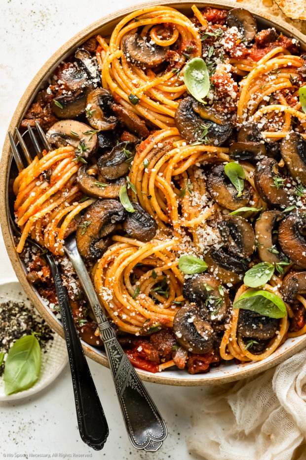 Overhead, close-up photo of a bowl of Mushroom Spaghetti garnished with fresh basil leaves and grated parmesan with a serving fork and spoon inserted into the pasta and a ramekin of crushed black pepper next to the bowl.