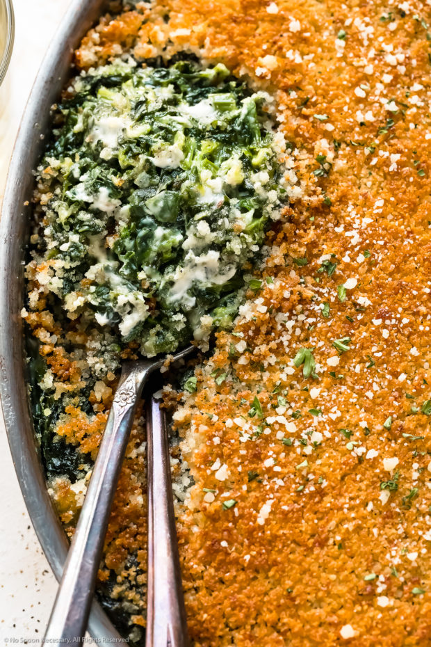 Slightly angled, close-up photo of Creamed Spinach Casserole in an oval baking pan with two serving spoons tucked into the casserole exposing the creamy spinach interior.