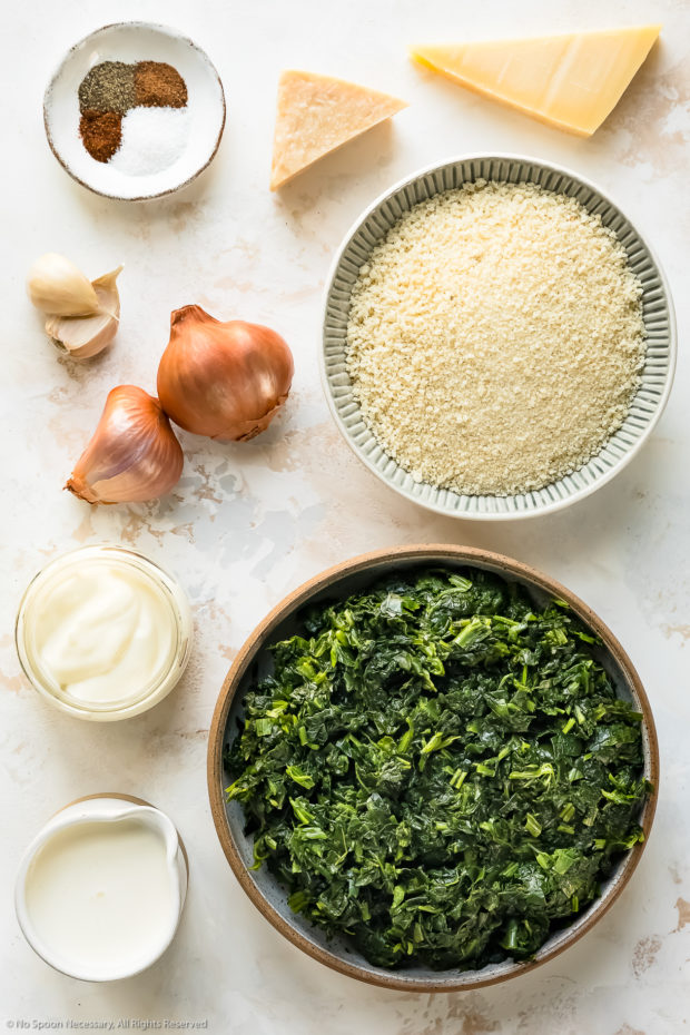 Overhead photo of all the ingredients in creamed spinach casserole neatly organized on a white surface.