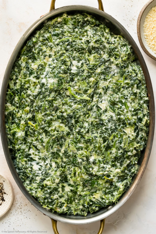 Overhead photo of creamed spinach in an oval baking dish before being topped with breadcrumbs.