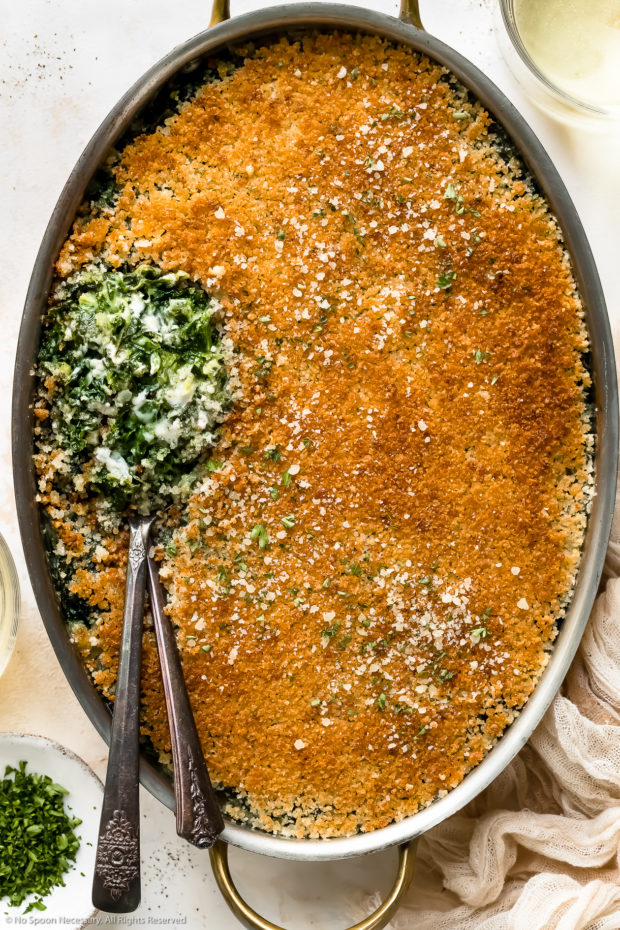 Overhead photo of Creamed Spinach Casserole in an oval baking pan with two serving spoons tucked into the casserole exposing the creamy spinach interior.