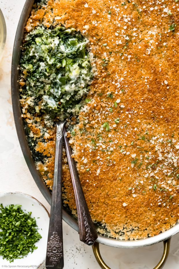 Overhead, close-up photo of Creamed Spinach Casserole in an oval baking pan with two serving spoons tucked into the casserole exposing the creamy spinach interior.