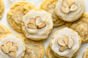 Overhead landscape photo of a spread out stack of soft and chewy almond sugar cookies on a white wood surface - the bottom cookies are plain while the cookies on top of the stack are covered with a cookie icing and decorative sliced almonds.