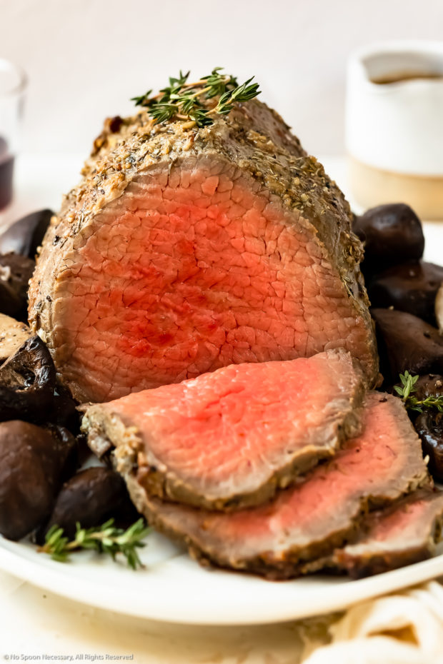 Straight on photo of a eye of round roast beef that's been sliced into to expose the pink medium-rare center.