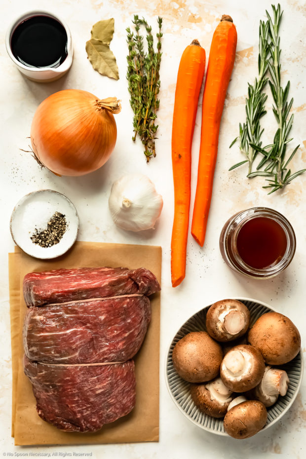 Overhead photo of all the ingredients needed to make eye of round roast beef recipe neatly organized by individual ingredient on a white surface.