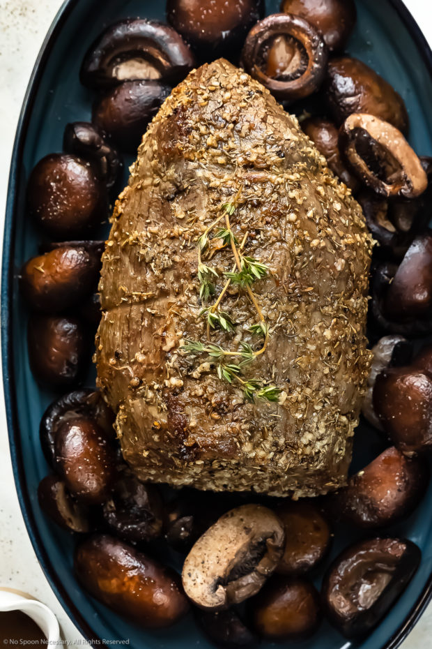 Overhead photo of a roasted whole eye of round beef roast on a bed of mushrooms in a blue roasting pan.