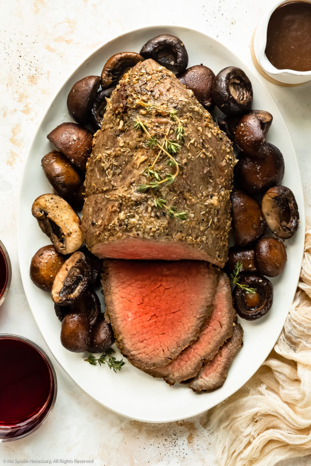 Overhead photo of a eye of round roast beef that's been partially sliced next to a bed of mushrooms on a white platter with a ramekin of gravy and red wine glasses next to the platter.
