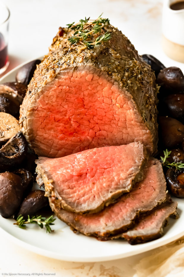 Slightly angled photo of a eye of round roast that's been partially sliced on a bed of mushrooms on a white platter.