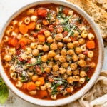 Overhead photo of Easy Vegetable and Chickpea Soup in a white bowl with slices of crusty bread, a ramekin of fresh basil and a pale tan napkin next to the bowl.