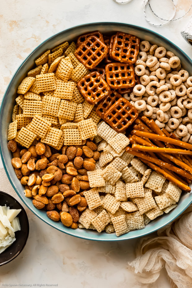Overhead photo of all the ingredients needed to make Chex snack mix neatly organized by individual ingredient in a large blue mixing bowl.