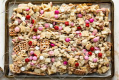 Overhead landscape photo of Sweet Chex Mix on a parchment-paper lined sheet pan.